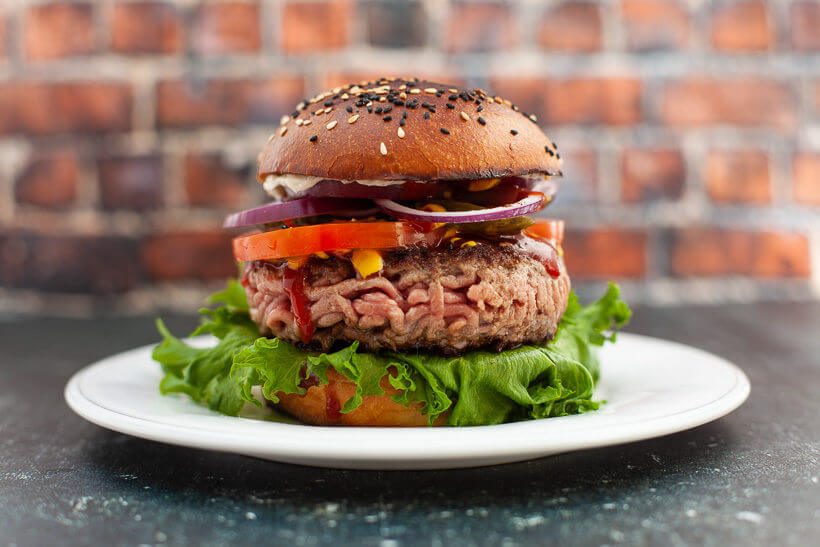 A delicious burger with a toasted brioche burger bun on a plate