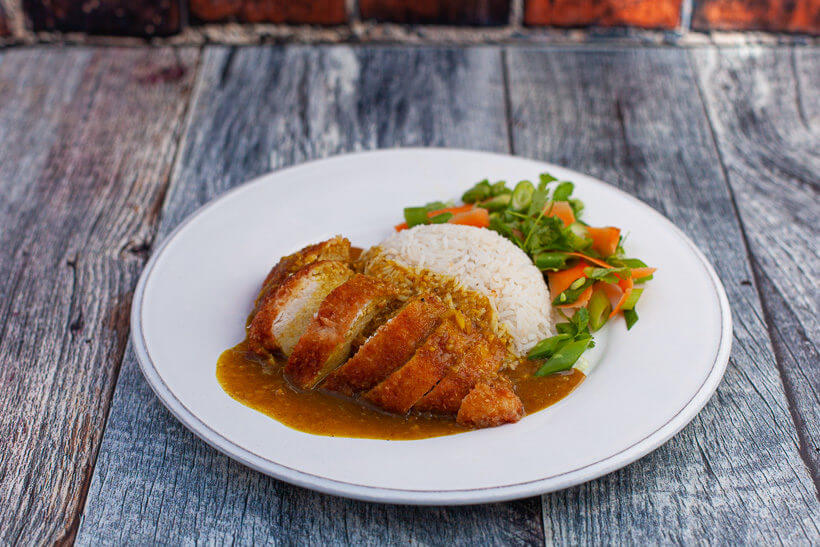 Chicken katsu curry on a plate with a salad on the side.