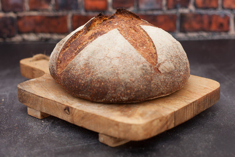 A sourdough loaf on a board in front of a brick wall scored gorgeously