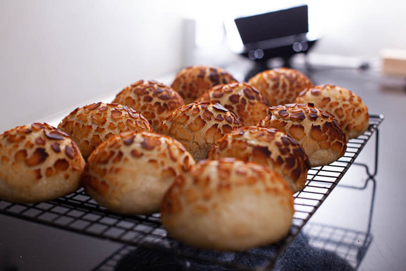 Sourdough tiger bread rolls cooling on a wire rack