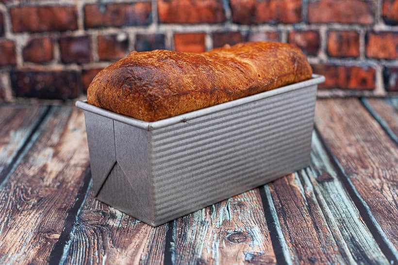 Blueberry swirl sourdough brioche bread in a small pullman loaf pan in front of a brick wall