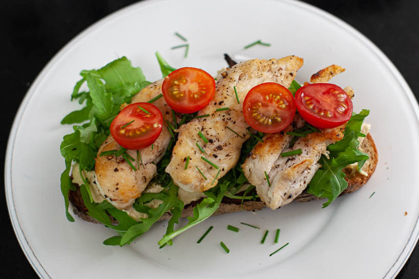toasted sourdough bread with hummus, pesto, arugula, fried chicken tenders and cherry tomatoes