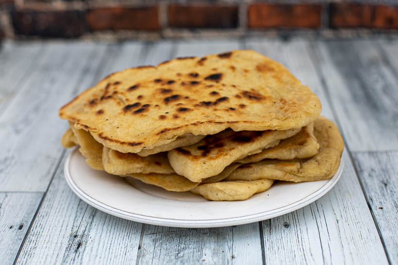 Sourdough naan bread on a plate on a wooden floor in front of a brick wall