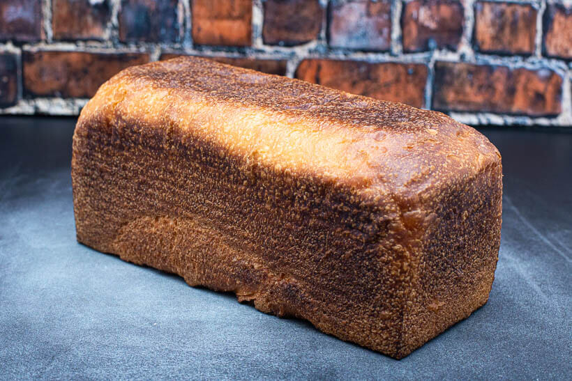 Sourdough sandwich bread baked in a pullman loaf pan on a concrete floor in front of a brick wall.