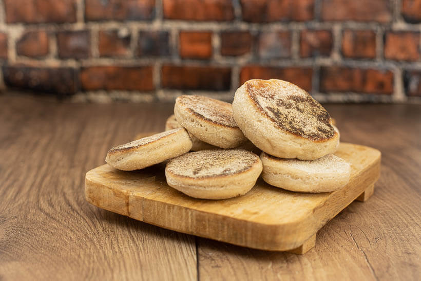 sourdough english muffins on a board in front of a brick wall