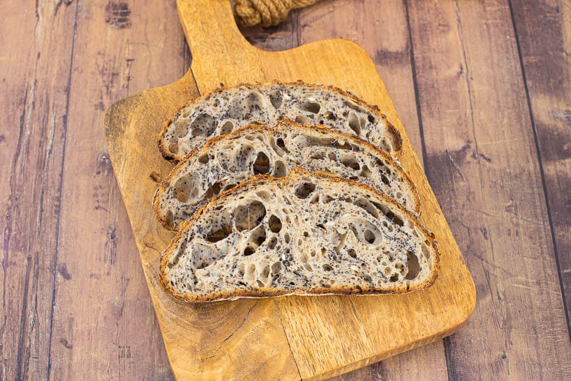 Three slices of gorgeous seeded sourdough bread on a wooden board